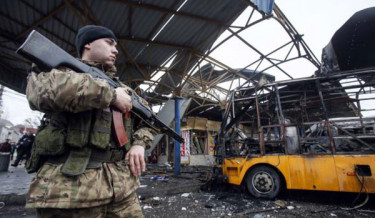 A member of the armed forces of the separatist self-proclaimed Donetsk People's Republic stands guard near a destroyed vehicle at a bus station after shelling in Donetsk, February 11, 2015.