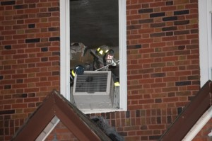 A Firefighter pulls an air conditioner from a window at the home where the 2-year-old boy was rescued.